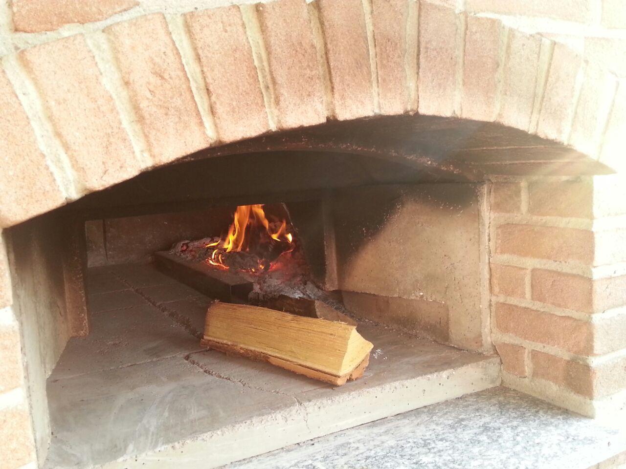 un forno con una fiamma accesa e della legna