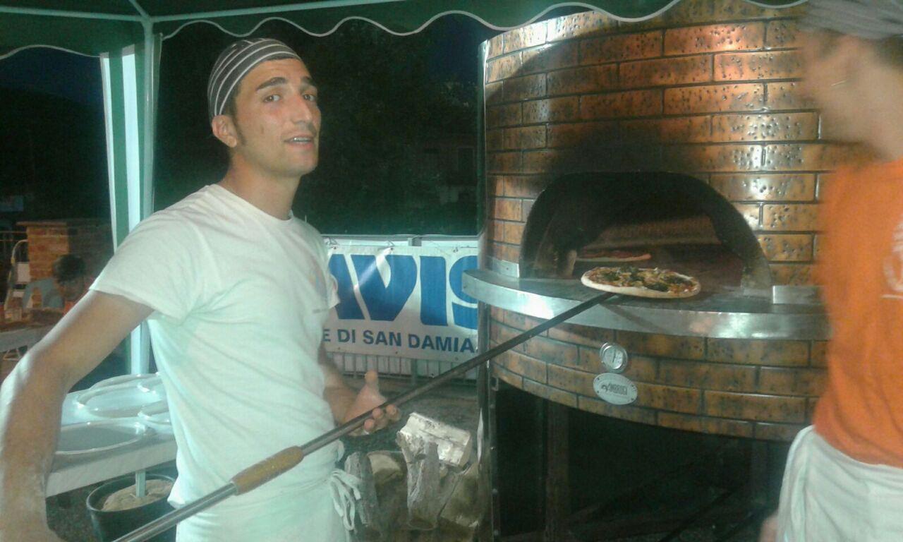 un pizzaiolo con una pala mentre inforna una pizza