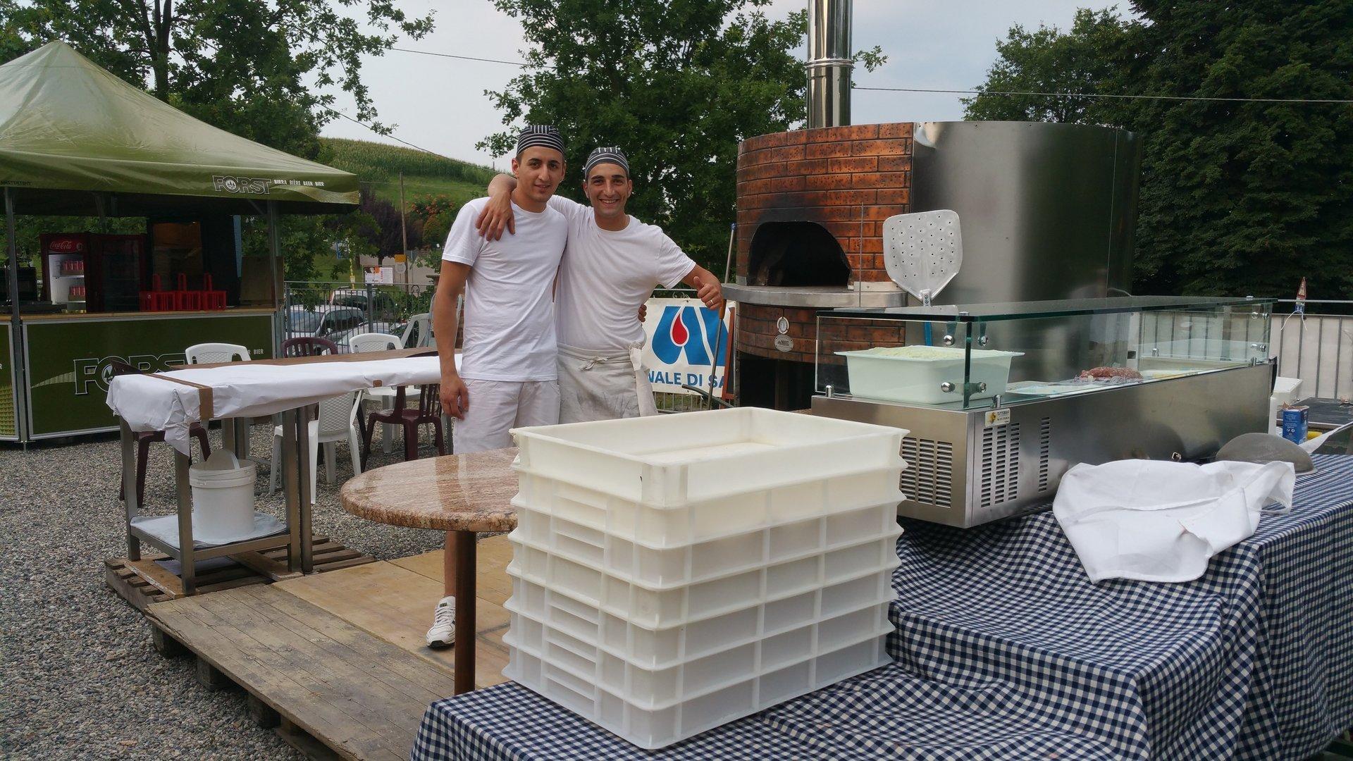due pizzaioli abbracciati in posa per una foto all'esterno