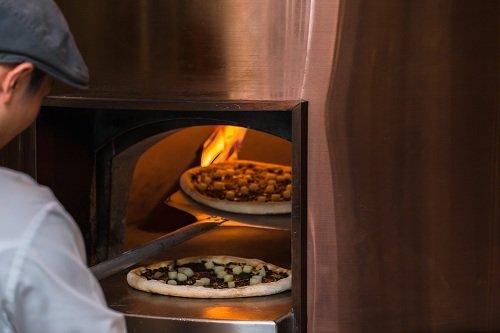 un pizzaiolo che inforna una pizza