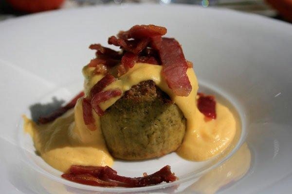 un piatto con una tortina e sopra della pancetta fritta tagliata a cubetti con della salsa gialla