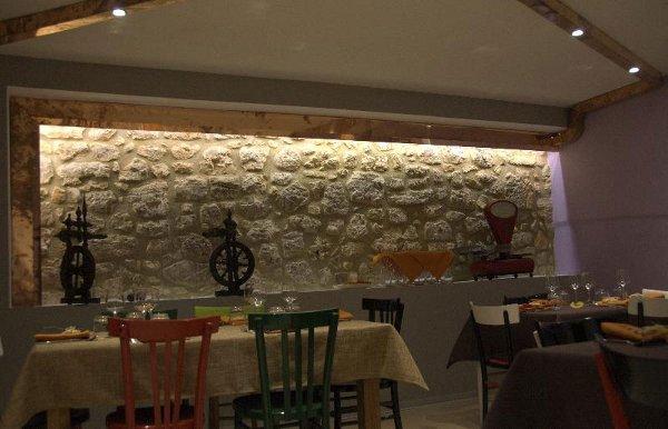 sala da pranzo all'interno di un agriturismo con tavoli apparecchiati con tovaglie beige e bordeaux, sedie verdi rosse e nere e vista di un muro in pietra e sotto degli oggetti esposti