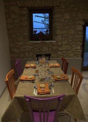 un tavolo con una tovaglia beige, tovaglioli arancioni, sedie viola, arancioni, rosse  e nere e di fronte una parete in pietra con una piccola finestrella con dei fiori
