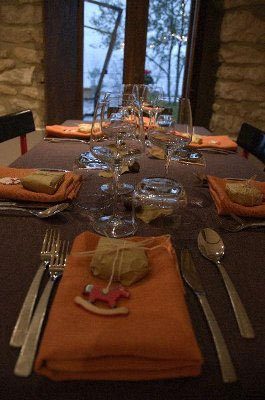 un tavolo apparecchiato con visuale focalizzata sui bicchieri di cristallo, le posate e i tovaglioli arancioni