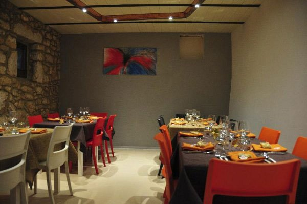sala da pranzo vista da un'altra angolazione con tavoli apparecchiati sedie colorate e su una parete un quadro blu con sfumature rosse