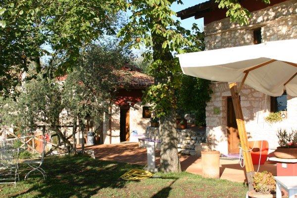 esterno del giardino dell'agriturismo con vista di un edificio in pietra, un albero, il prato e sulla destra si intravede un ombrellone color panna sorretto da una base di legno
