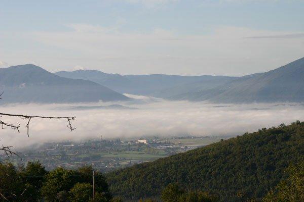 vista del paesaggio collinare,la cittadine con della nebbia e in lontananza dei monti