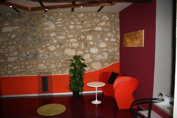 una sala con una parete in pietra sotto verniciata in arancione lucido,un vaso con una pianta, sulla destra due sedie arancioni e un tavolino bianco al centro