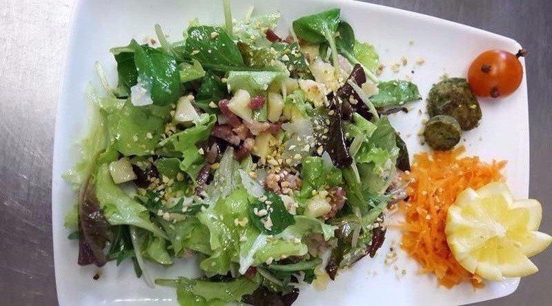 insalata mista con scaglie di pinoli, limone tagliato a forma di stella e carote