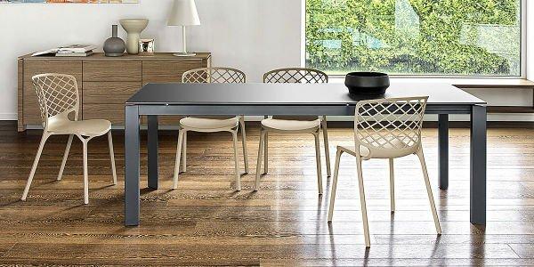 un tavolo nero con delle sedie beige