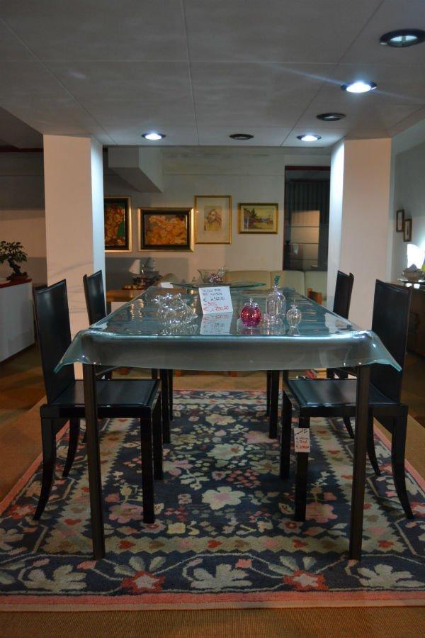 un tavolo di vetro e delle sedie nere