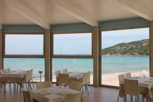 tavoli e sedie all'interno del ristorante con vista del mare