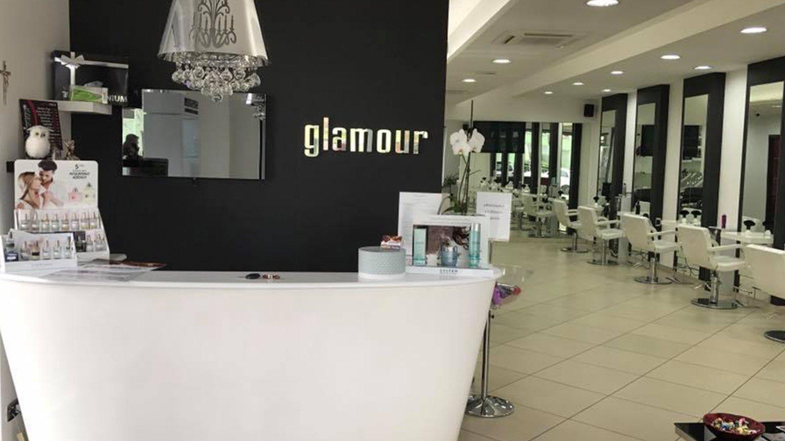 vista di un banco bianco, la scritta Glamour e le sedie all'interno di un negozio di parrucchieri