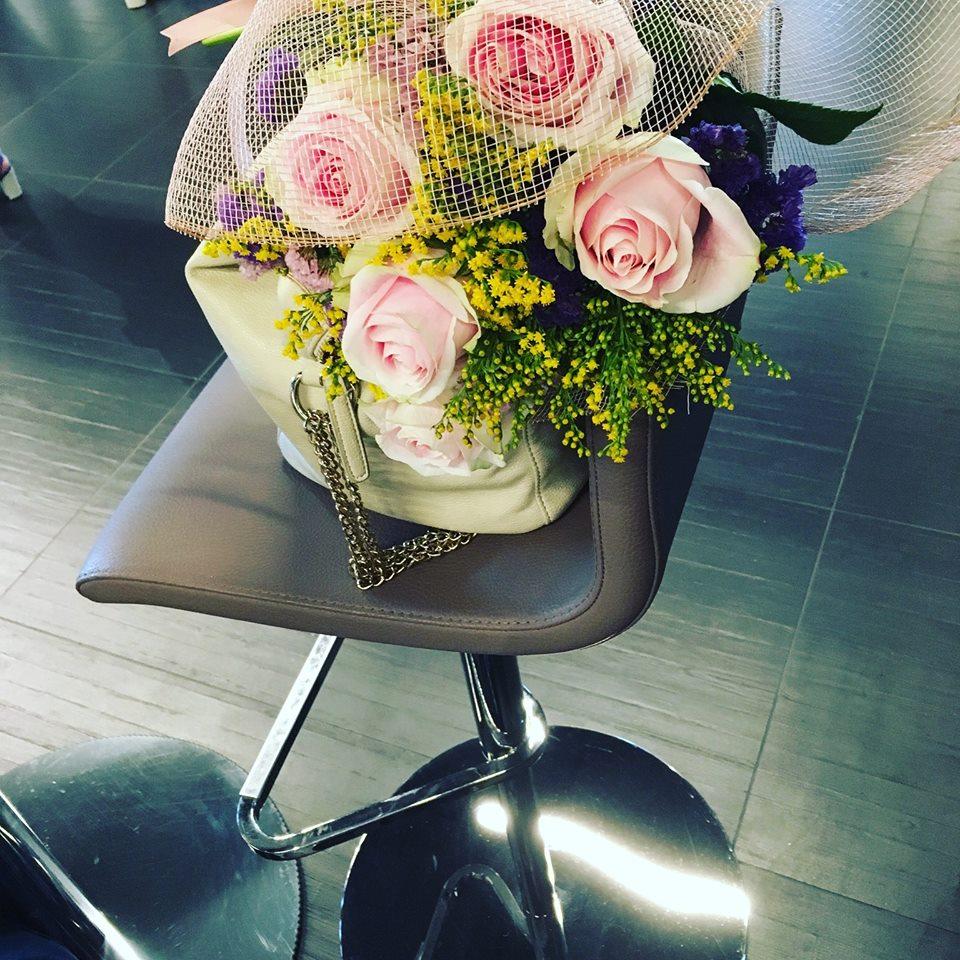 composizione di rose rosa in un contenitore di paglia su una sedia