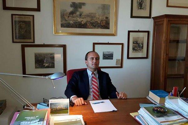 Nello studio, un avvocato alla scrivania  con una cravatta a righe bianche e rosse e davanti a lui un foglio con appoggiata una penna