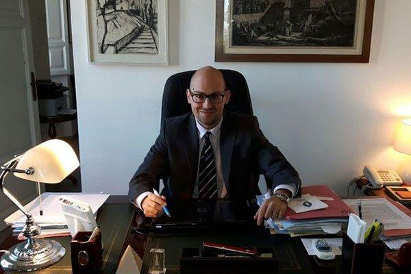 Un signore con gli occhiali, alla scrivania con una penna in mano sorride mentre gli scattano una foto