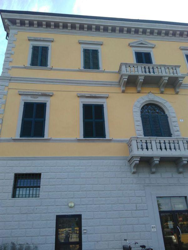 Vista di una palazzina con facciata di color giallognolo con dei balconi e delle persiane