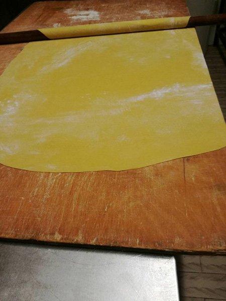 un impasto di color giallo steso su un tagliere di legno