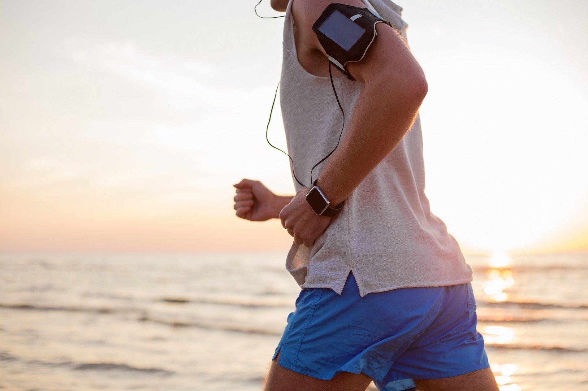 Giovane correndo porta nel braccio un apparecchio per controllare i suoi battiti,pulsazioni e lo sforzo realizzato nella sua carriera