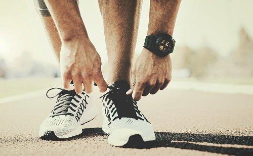 Atleta allacciandosi  le scarpe sportive