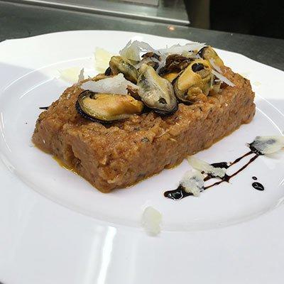 un tortino di risotto ai frutti di mare con sopra delle cozze sgusciate
