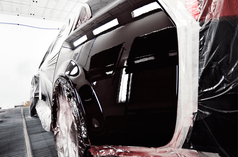 Black Nissan receiving car spray painting services in Brisbane