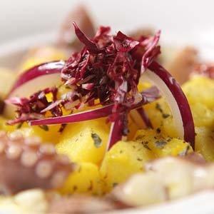 un piatto di polipo con patate e una foglia di insalata rossa