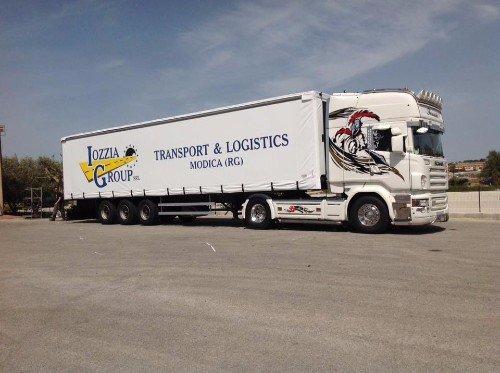 Un tir con un rimorchio con scritto Iozzia Group transport & logistics