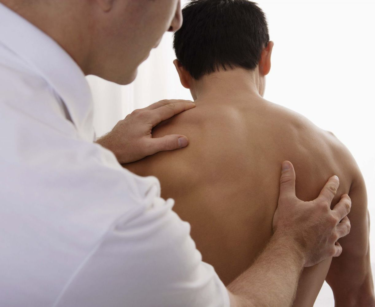Chiropractor center works on spine alignment with a patient in Anchorage, AK