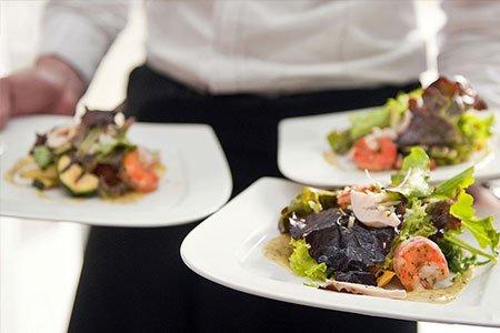 un cameriere con dei piatti di insalata con gamberi