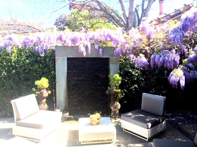 patio with wisteria framed stone waterfall
