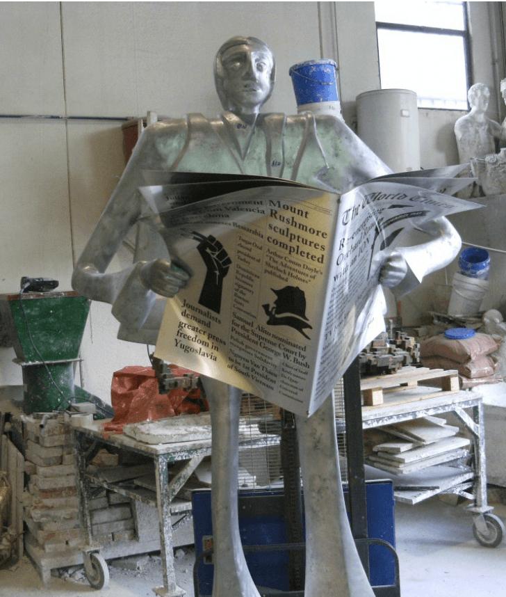 statua uomo che legge il giornale
