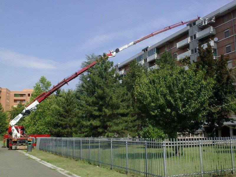 un lungo braccio meccanico che dalla strada arriva a un condominio