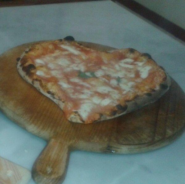 una pizza a forma di cuore su un tagliere