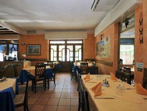 ristorante con pareti decorate, dettagli in legno e colori pastello