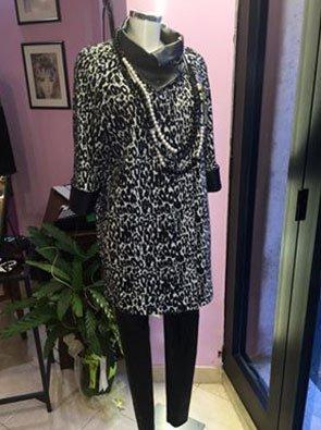 un manichino con una giacca bianca e nera leopardata e dei pantaloni neri