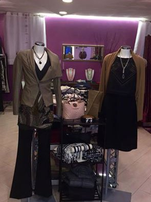 Due manichini con esposizioni di abiti di color nero e grigio all'interno di una boutique