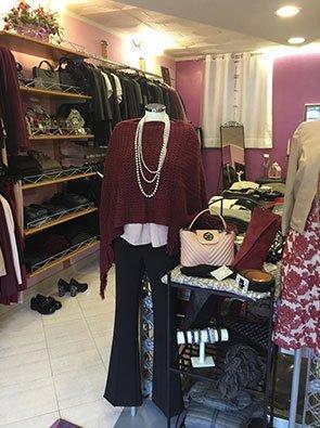 Interno di un negozio di abbigliamento con manichini, mensole con borse e altri oggetti