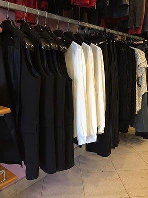 Un appendiabiti a muro con delle giacche nere, camicie bianche e pantaloni neri appesi