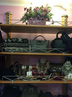 uno scaffale con mensole in legno, borse in esposizione e altri oggetti e in alto un vaso di fiori viola