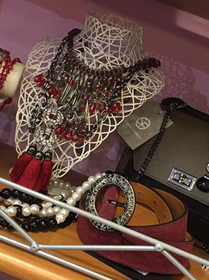 collane bordeaux con pon pon rossi, collane con perle bianche e nere e di fianco una borsa e una cintura bordeaux arrotolata