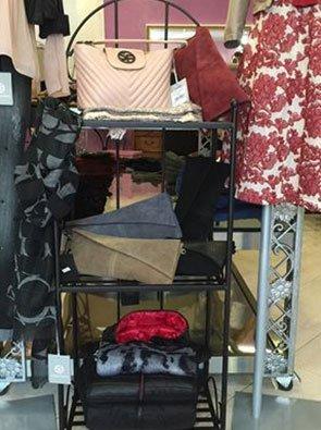 piccolo scaffale in ferro di color nero con borse beige,nere, rosa e bordeaux e accanto un vestito bianco a fiori rossi