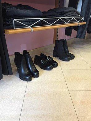una mensola con sopra dei pantaloni piegati e sotto delle scarpe e degli stivaletti neri