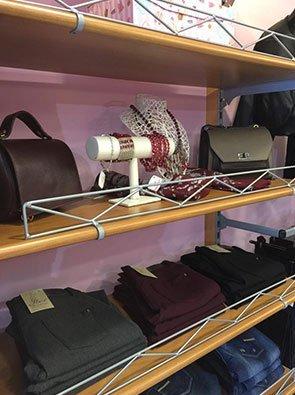 4 mensole, due con jeans e pantaloni piegati di color bordeaux grigio e nero,una con delle borse e una vuota