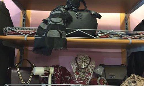 vista ravvicinata di uno scaffale con mensole in legno e metallo e borse nere e bordeaux