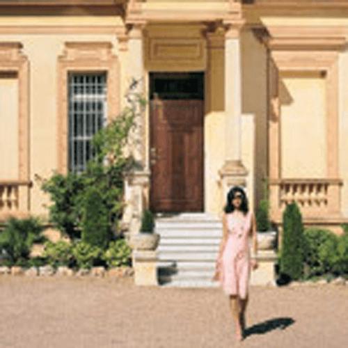 costruzione con porta esterna in legno e davanti donna che cammina