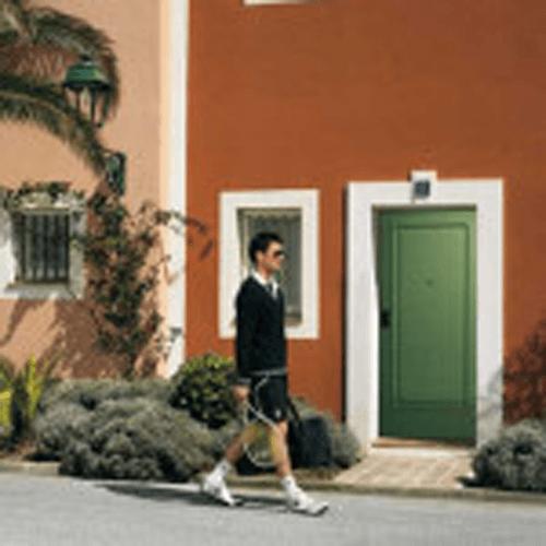 giocatore di tennis passeggia davanti a una costruzione marrone e porta verde