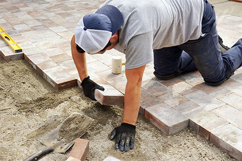 Worker adding pavement bricks