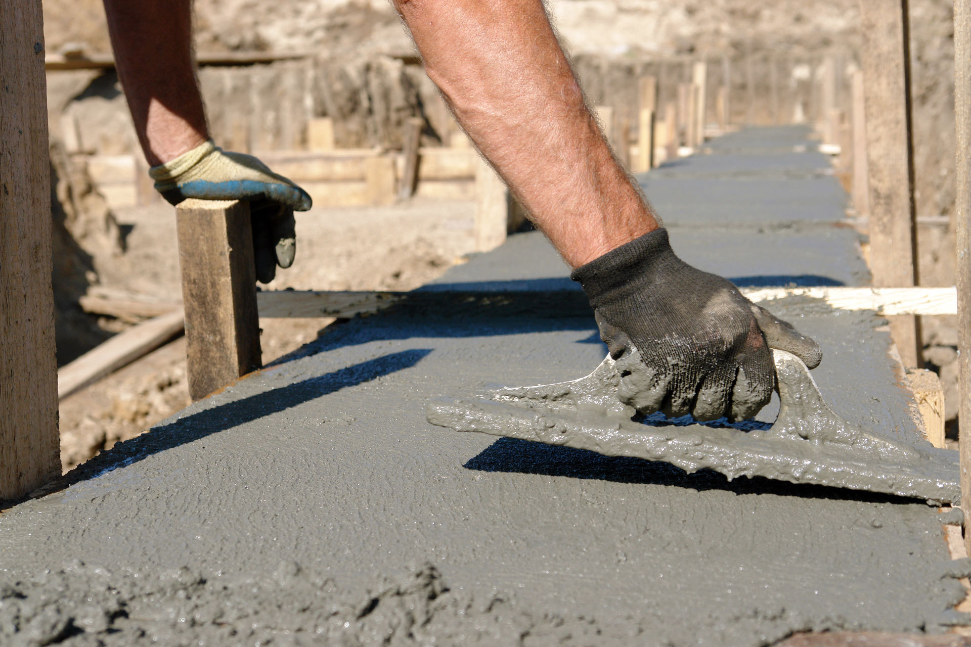 worker applying concrete base