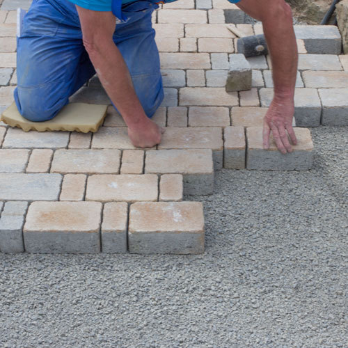 worker adding pavements to a driveway